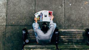 man reading community newspaper
